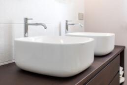 doppio lavabo-da-appoggio-in-ceramica-bianca-su-mobile-bagno-in-legno-duro